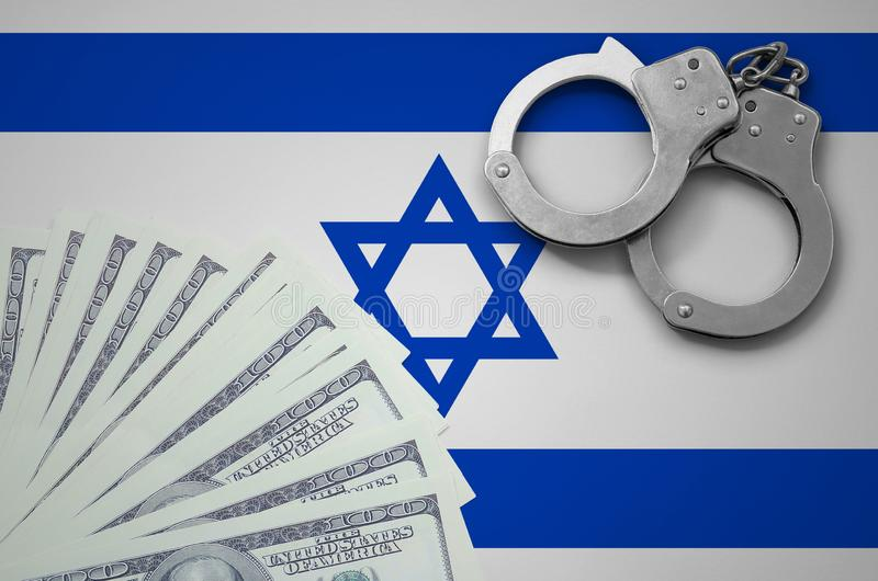 Israel flag with handcuffs and a bundle of dollars. The concept of illegal banking operations in US currency stock photos