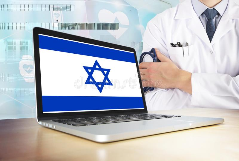 Israel healthcare system in tech theme. Israeli flag on computer screen. Doctor standing with stethoscope in hospital. Cryptocurrency and Blockchain concept stock photo