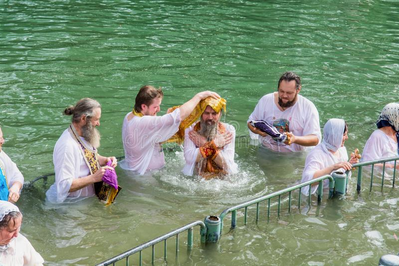 Israel / Jordan River - 03.26.2016: Christian pilgrims during the baptism ceremony on the Jordan River in Northern Israel the royalty free stock photo