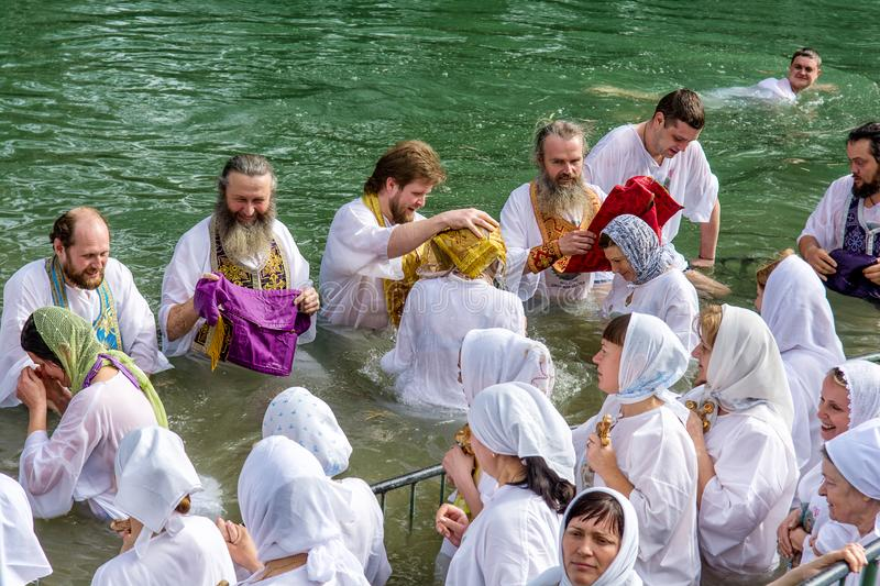 Israel / Jordan River - 03.26.2016: Christian pilgrims during the baptism ceremony on the Jordan River in Northern Israel the royalty free stock images