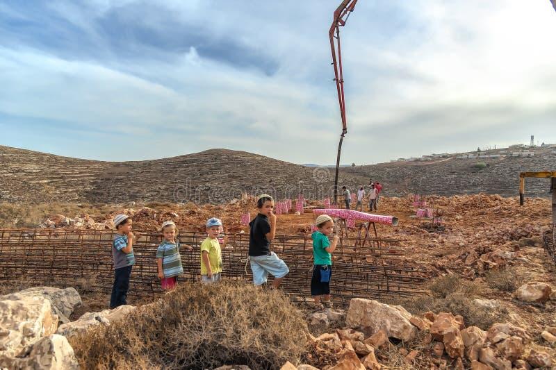Israel Judea-Wüste am 24. Oktober 2015 Jüdische Siedlerkinder passen als das illegal besetzte Land in der Regelung mit agricul au lizenzfreie stockfotografie