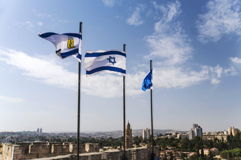 Israel och Jerusalem flaggor på Jerusalem gamla stadsväggar mot den blåa himlen med vita moln i soligt sommarljus royaltyfri bild
