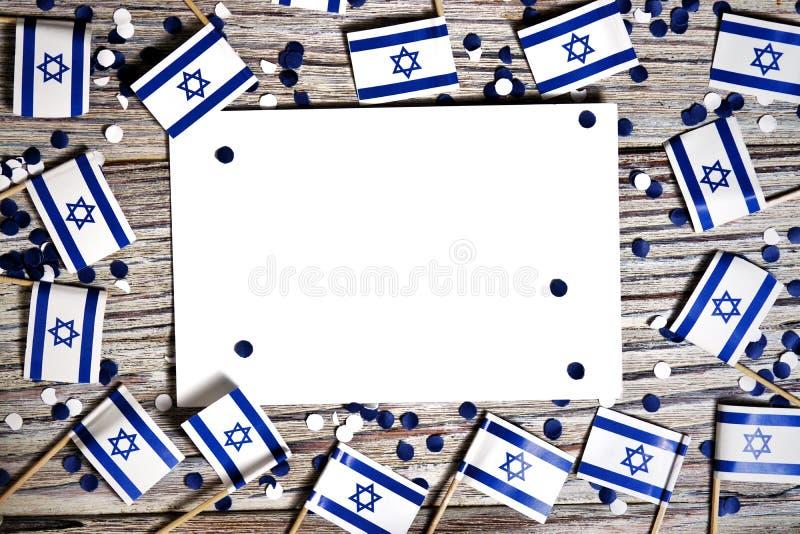 Israel-Unabh?ngigkeitstag 29. April 2020 weißes blaues Konfettipapier mit Mini-Israel-Flaggen und weißes Blatt Papier auf Weiß lizenzfreies stockfoto