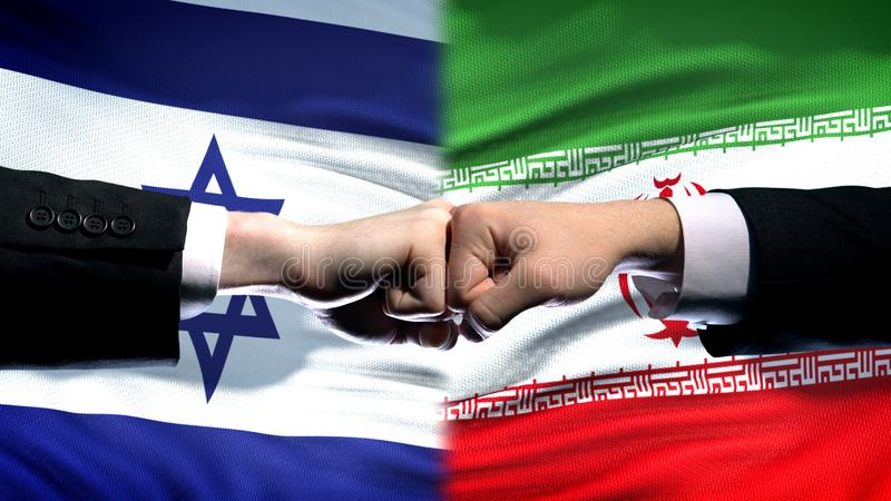 Israel vs Iran conflict, international relations, fists on flag background. Stock photo royalty free stock photography