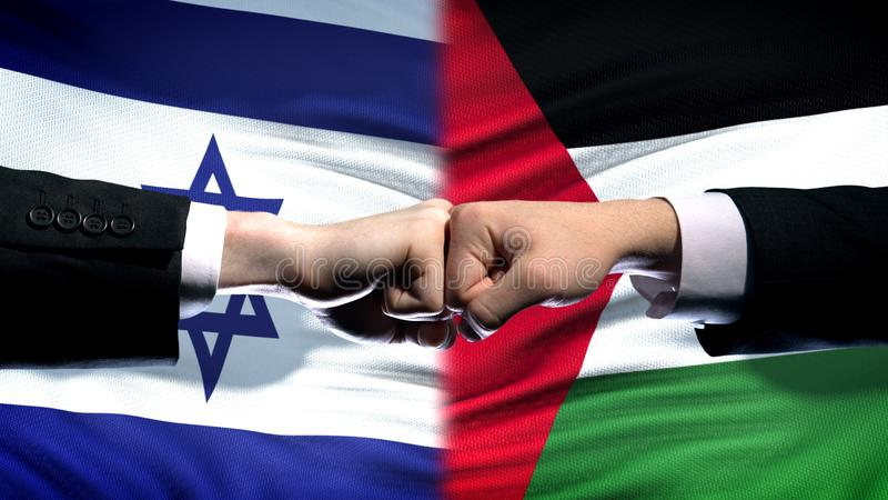 Israel vs Palestine conflict, international relations, fists on flag background. Stock photo royalty free stock images