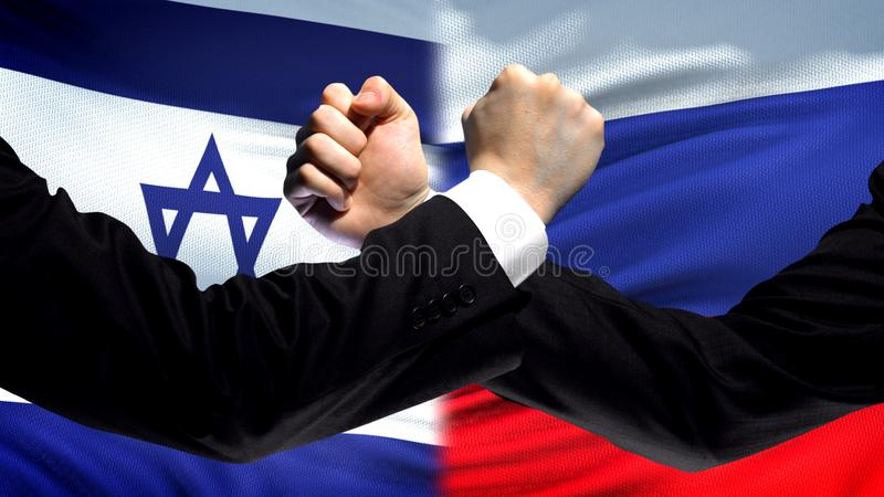 Israel vs Russia confrontation, countries disagreement, fists on flag background. Stock photo royalty free stock photography