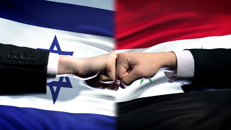 Israel vs Syria conflict, international relations, fists on flag background. Stock photo royalty free stock photo