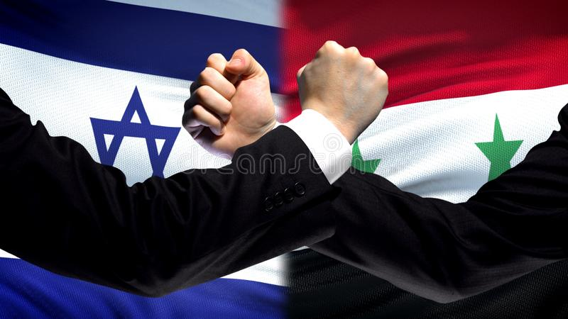 Israel vs Syria confrontation, countries disagreement, fists on flag background. Stock photo stock image