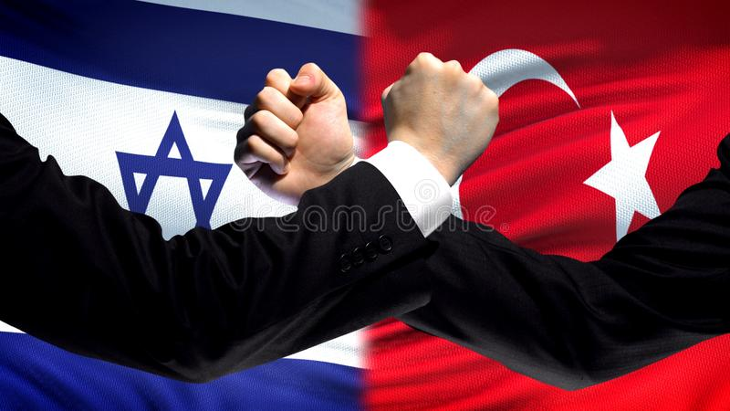 Israel vs Turkey confrontation, countries disagreement, fists on flag background. Stock photo stock photo