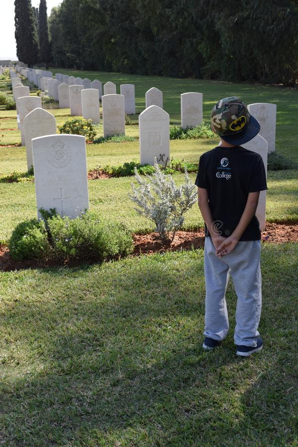 Israele, Ramle, 2018 - un ragazzo in un cappello sta con il suo di nuovo al cimitero fotografie stock libere da diritti