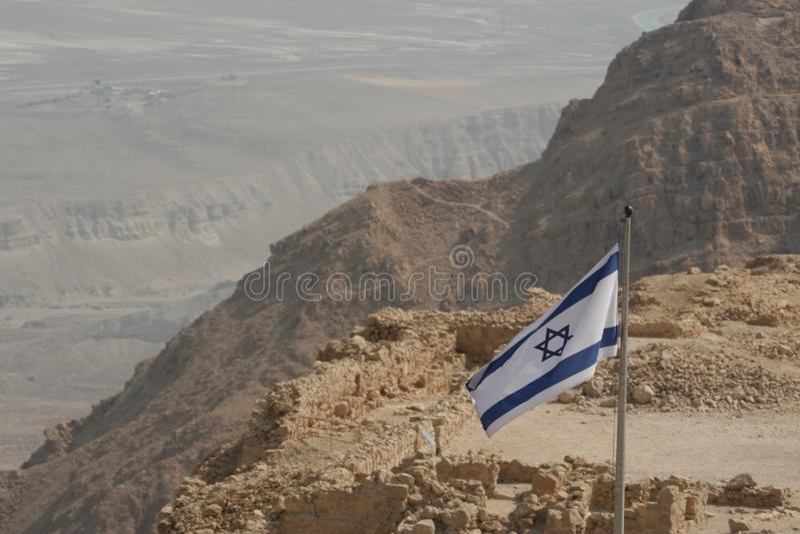 Israelen sjunker på ett ökenberg (Masada)