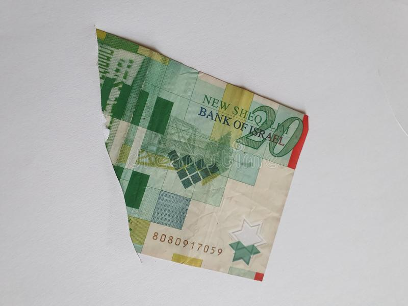 Israeli banknote of twenty shekels on the broken sheet of paper. Commerce, exchange, trade, trading, value, buy, sell, profit, price, rate, cash, currency stock photos