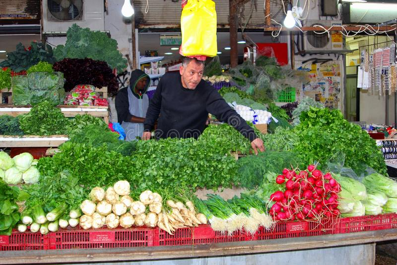 Israeli man sells fresh vegetables Carmel market, Tel Aviv royalty free stock photo