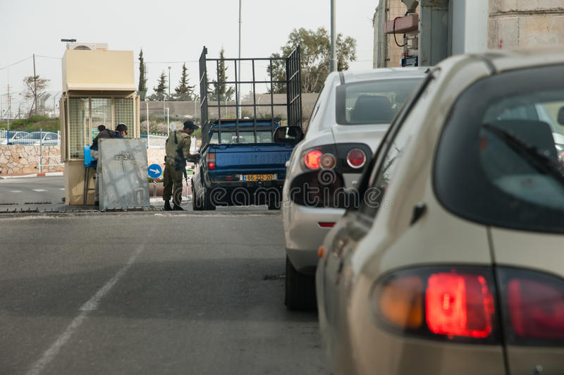 Israeli military checkpoint. A soldier checks cars passing through the Israeli military checkpoint controlling movement between Bethlehem and Jerusalem through stock photography