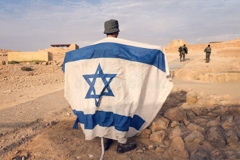 Israelische Militärinfanterie steht in der Mitte der Wüste, die eine israelische Flagge mit dem Davidsstern hält Jüdischer Patrio stockfotos