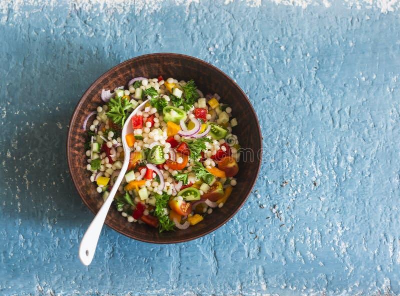 Israelisk cous cous sallad för ptitimgrönsaktabbouleh på en blå bakgrund, bästa sikt Vegetarisk mat arkivbilder
