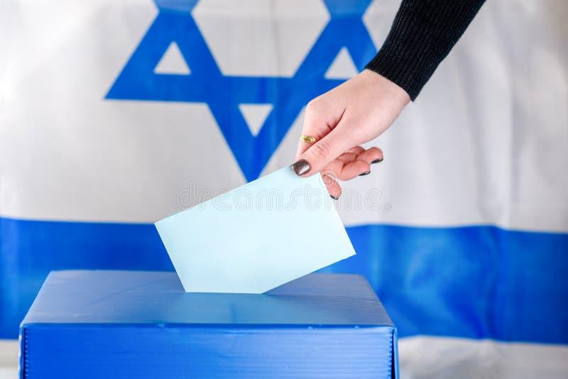 Israelisk ung kvinna som sätter en sluten omröstning i en valurna på valdag arkivbild