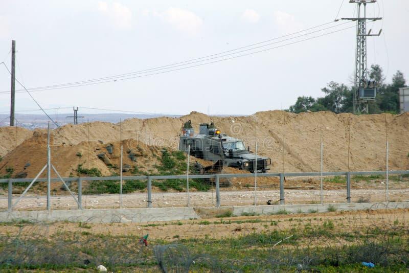 Israeliska styrkor ingriper i palestinier under demonstrationerna nära denIsrael gränsen, i den sydliga Gazaremsan royaltyfri fotografi