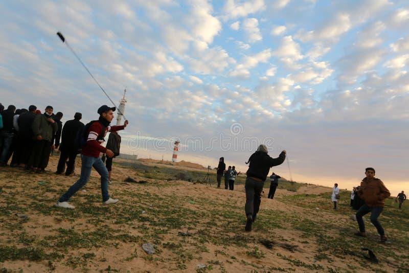 Israeliska styrkor ingriper i palestinier under demonstrationerna nära denIsrael gränsen, i den sydliga Gazaremsan arkivfoton