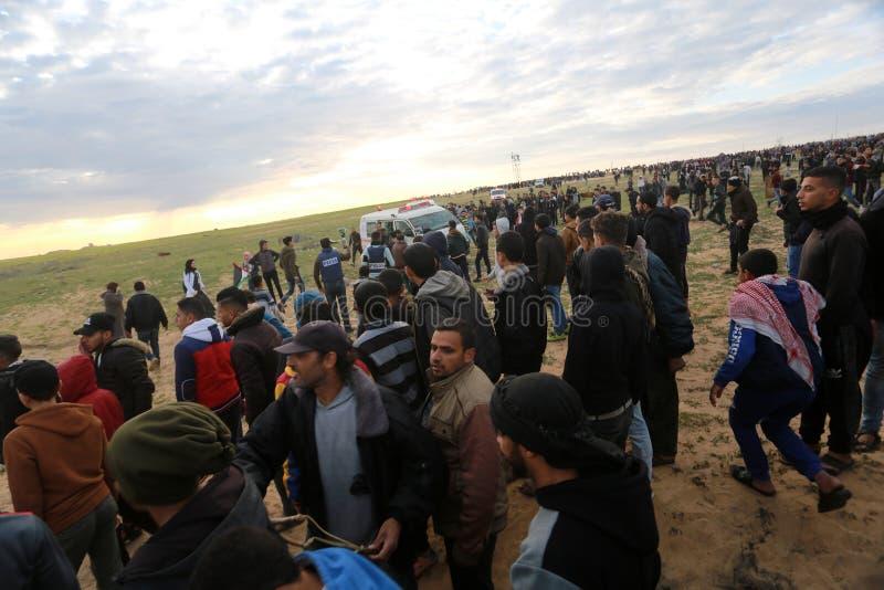 Israeliska styrkor ingriper i palestinier under demonstrationerna nära denIsrael gränsen, i den sydliga Gazaremsan royaltyfri foto