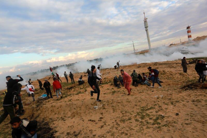 Israeliska styrkor ingriper i palestinier under demonstrationerna nära denIsrael gränsen, i den sydliga Gazaremsan arkivfoto
