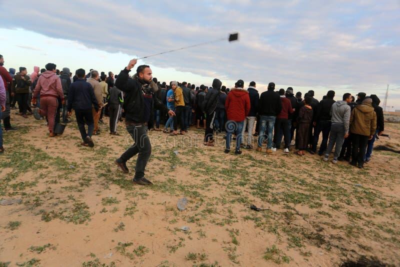 Israeliska styrkor ingriper i palestinier under demonstrationerna nära denIsrael gränsen, i den sydliga Gazaremsan royaltyfri bild