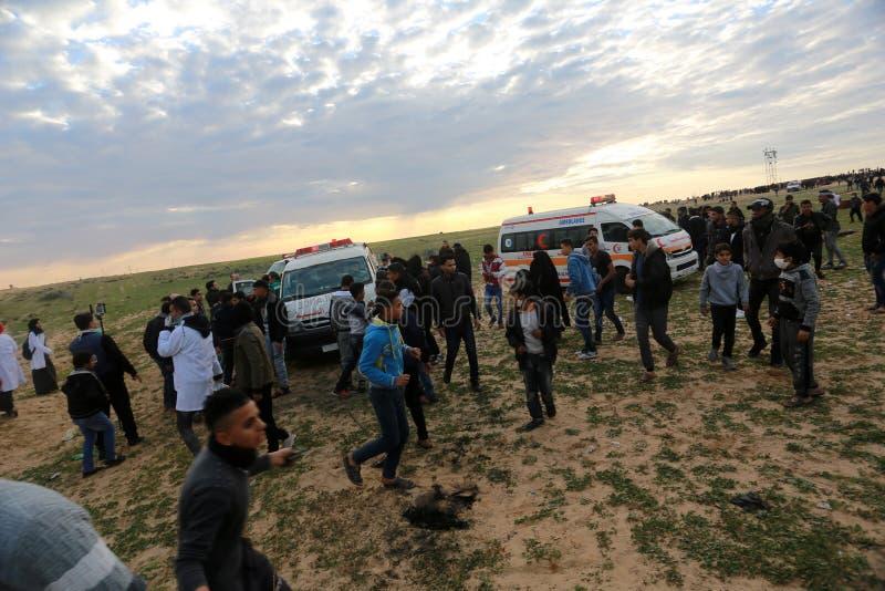 Israeliska styrkor ingriper i palestinier under demonstrationerna nära denIsrael gränsen, i den sydliga Gazaremsan royaltyfria bilder
