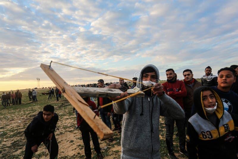 Israeliska styrkor ingriper i palestinier under demonstrationerna nära denIsrael gränsen, i den sydliga Gazaremsan fotografering för bildbyråer