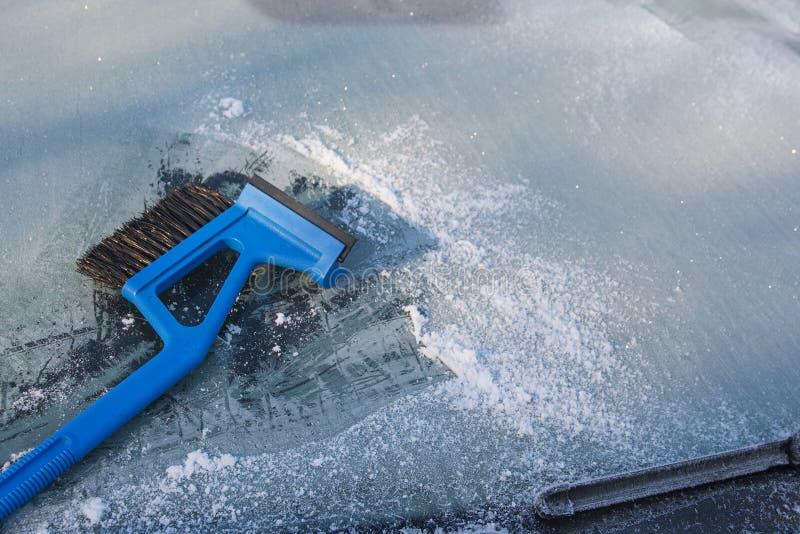 Isskrapa som gör ren en djupfryst vindruta av en bil, vintertraffi fotografering för bildbyråer