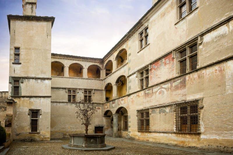 Issogne: Kasteel van Issogne De binnenplaats met de granaatappelfontein Val D ` Aosta, Italië stock foto's
