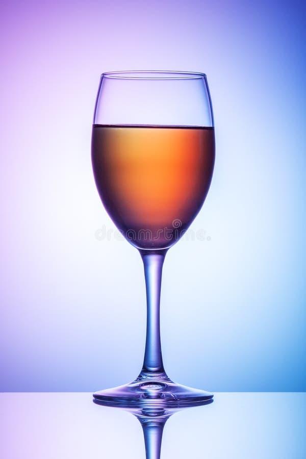 Ist auf dem Tisch ein Glas Wein auf einem farbigen Hintergrund lizenzfreie stockfotos