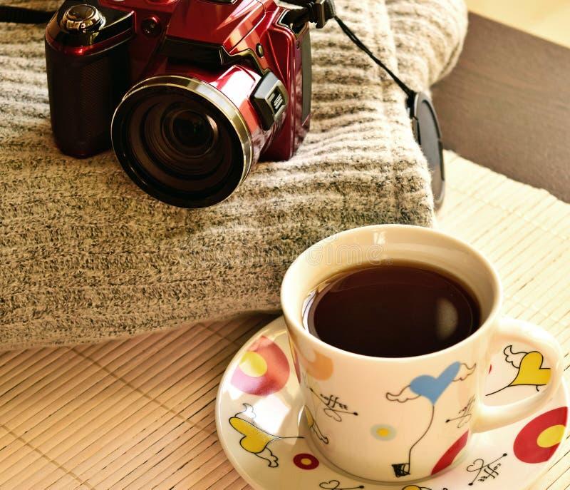 Ist auf dem Tisch eine Tasse Tee Kaffee, ist als Nächstes ein woolen Stoff und eine Kamera lizenzfreie stockbilder