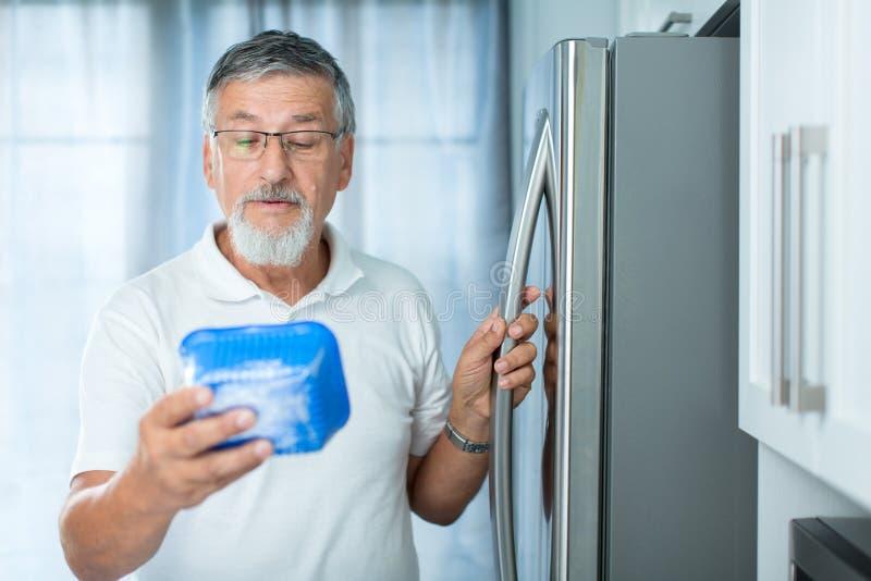 Ist dieses noch fein? Älterer Mann in seiner Küche lizenzfreies stockbild