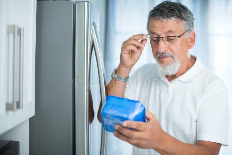 Ist dieses noch fein? Älterer Mann in seiner Küche durch den Kühlschrank lizenzfreies stockfoto