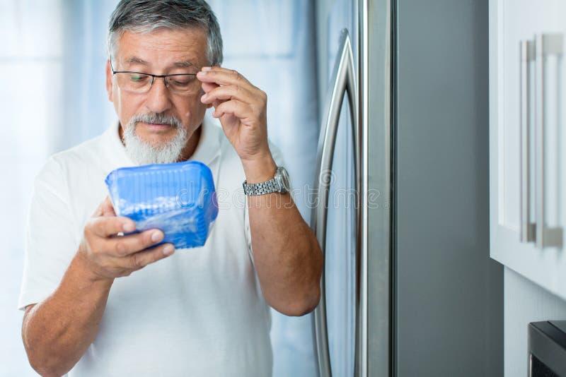 Ist dieses noch fein? Älterer Mann in seiner Küche durch den Kühlschrank stockfoto