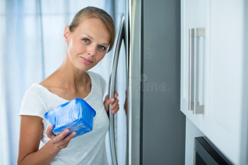 Ist dieses noch fein? Hübsche, junge Frau in ihrer Küche stockbild