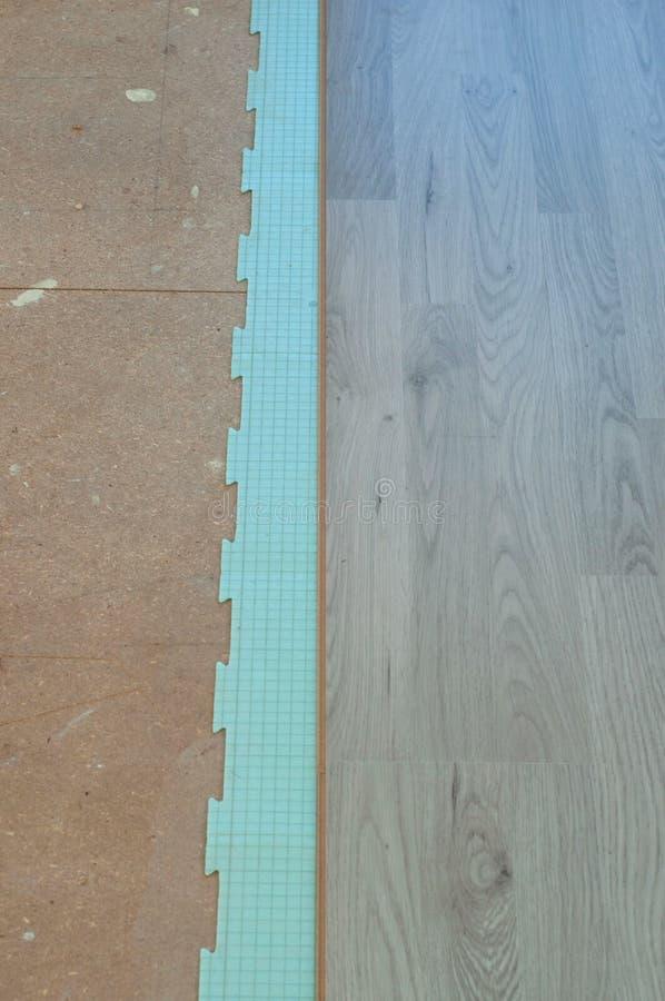 Istalation van nieuwe gelamineerde bevloering, die een het isoleren correct materiaal gebruiken royalty-vrije stock afbeeldingen