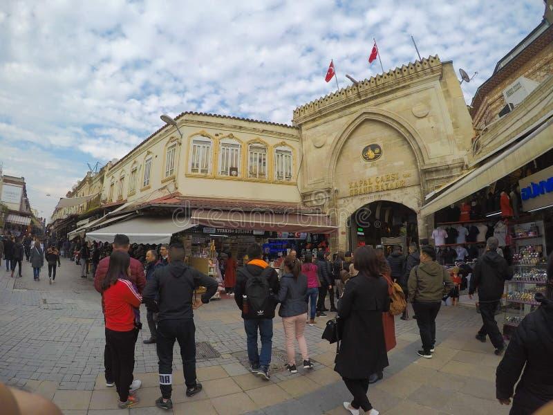 Istambul, Turquia - 8 de março de 2019: A compra dos povos na feira grande, os descansos feitos a mão, os sacos e os tapetes estã imagem de stock
