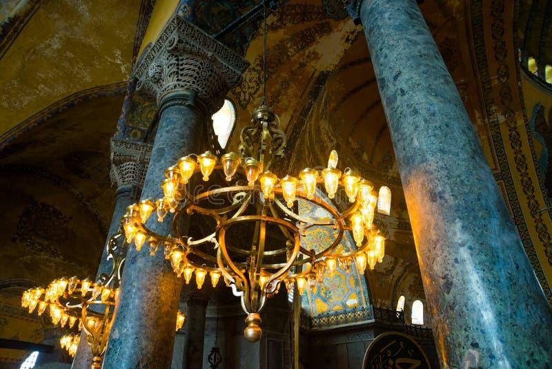 ISTAMBUL, TURQUIA: Interior de Hagia Sophia Candelabro velho do metal com as ampolas entre colunas imagem de stock royalty free