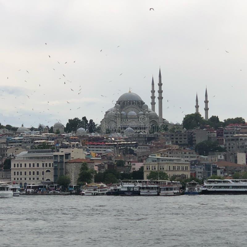 ISTAMBUL, TURQUIA: O cruzeiro ferries no porto de Eminonu perto de Yeni Cami e da ponte de Galata imagem de stock
