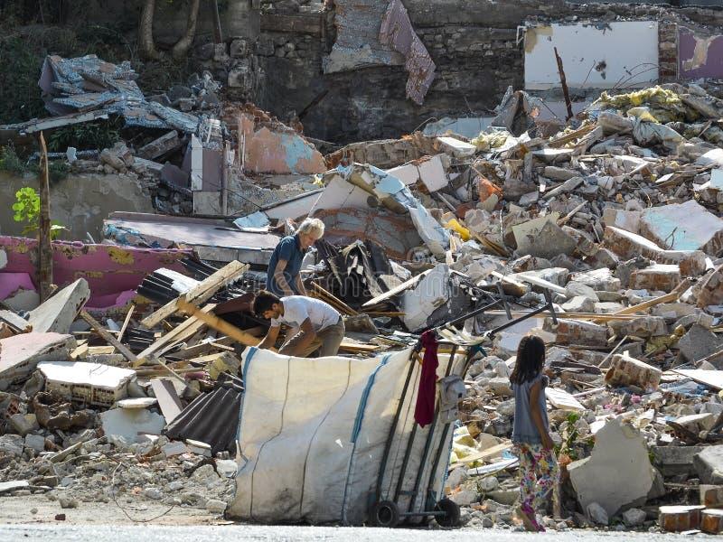 Istambul, TURQUIA, o 20 de setembro de 2018 As pessoas idosas, homens novos e menina recolhem o lixo nas ruínas de uma casa destr foto de stock