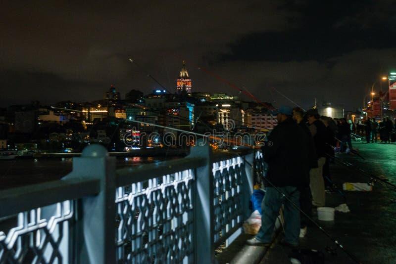 Istambul, Turquia: Os pescadores travam peixes da ponte, hastes longas Paisagem da noite com o mar e a vista bonita do Galat imagens de stock