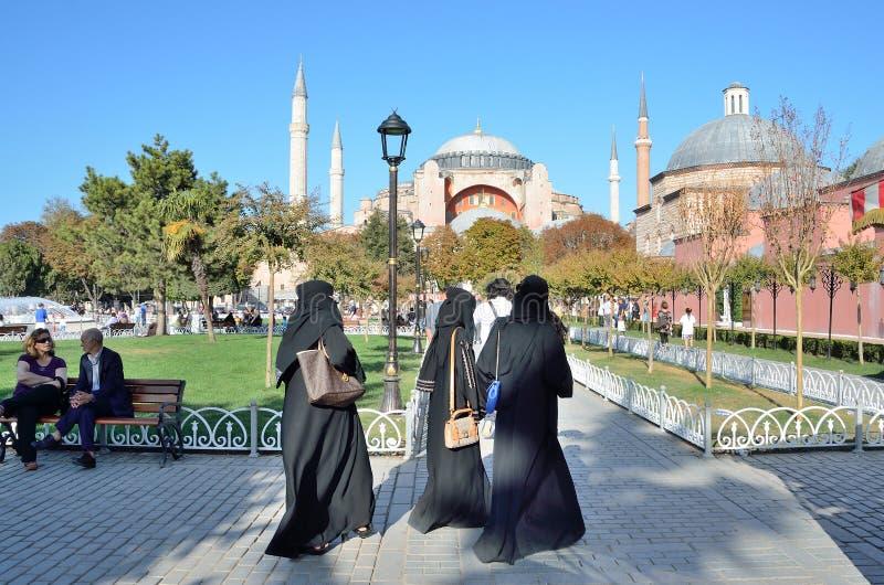 Istambul, Turquia, outubro, 18, 2013 Mulheres na roupa islâmica tradicional que andam perto de Aya Sofya fotos de stock royalty free