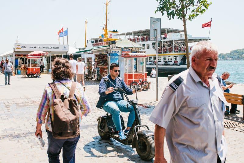 Istanboel, 17 Juni, 2017: Een kerel of een jonge mens drijven onderaan de stadsstraat op een elektrische autoped of een fiets Dic royalty-vrije stock afbeelding