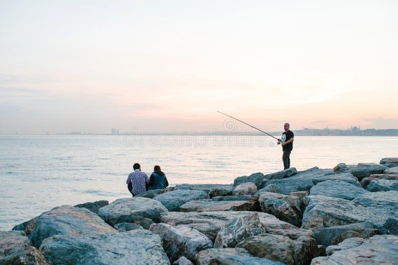 Istanboel, 14 Juni, 2017: Twee vrienden zitten op de kust dichtbij het overzees, delen en genieten van de mening van Bosphorus me royalty-vrije stock foto's