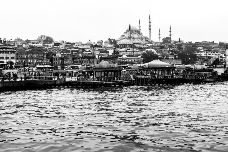 Istanboel, Turkije - December 6, 2014: De Suleymaniye-Moskeemening van Gouden Hoorn, mensen bezoekt de koffie in boten en horloge stock foto