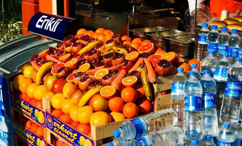 ISTANBOEL, TURKIJE - FEBRUARI 24 2009: Opslag die verse vruchten granaatappels, sinaasappelen, appelen en bananen en plastic fles stock afbeelding