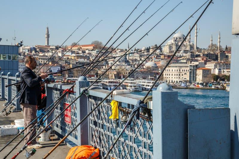 Istanboel, Turkije - Maart 22, 2019: Een lokale visser die op de Galata-Brug in Istanboel, Turkije vissen De brug van Galata royalty-vrije stock fotografie
