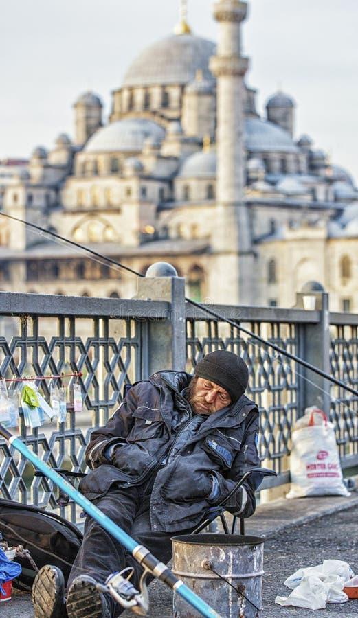 Istanbuł Turcja, Kwiecień 1,/, 2016 - mężczyzna śpi podczas gdy łowiący z mostu obrazy royalty free