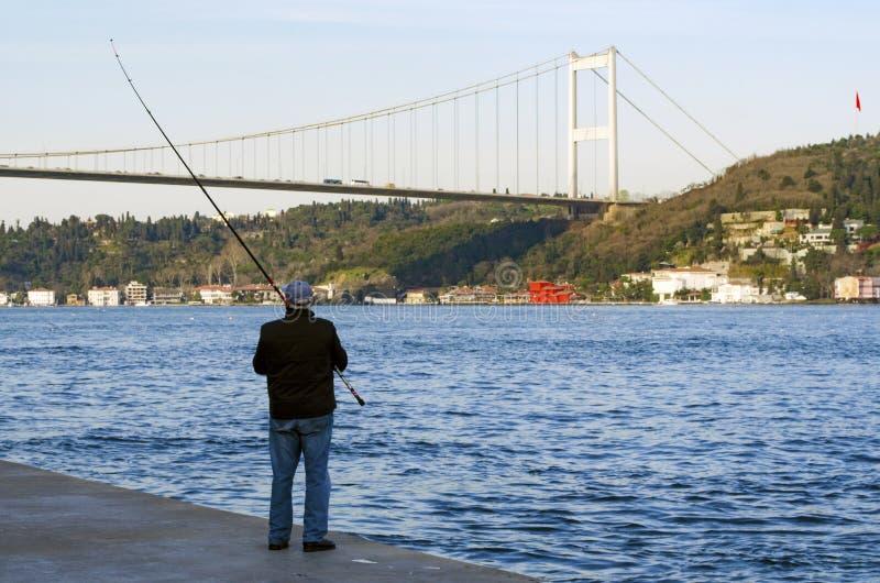 Istanbul bosphorus, fishing rod with the fish hunting. Istanbul, Turkey - March 18, 2013: Istanbul at the Bosphorus bonito, bluefish, mackerel, sardines, sea royalty free stock image